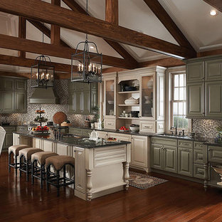 Large traditional l-shaped open plan kitchen in Orlando with an undermount sink, raised-panel cabinets, green cabinets, granite benchtops, multi-coloured splashback, glass tile splashback, stainless steel appliances, medium hardwood floors, with island and brown floor.