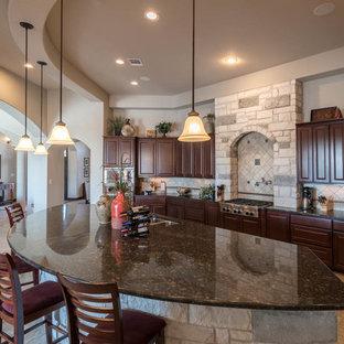 オースティンの大きい地中海スタイルのおしゃれなキッチン (ダブルシンク、シェーカースタイル扉のキャビネット、濃色木目調キャビネット、御影石カウンター、ベージュキッチンパネル、石タイルのキッチンパネル、シルバーの調理設備の、磁器タイルの床) の写真