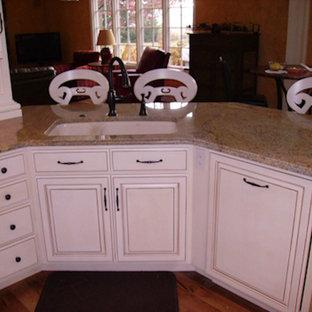 Küche mit Schrankfronten mit vertiefter Füllung, Schränken im Used-Look, Granit-Arbeitsplatte, bunter Rückwand, Rückwand aus Steinfliesen, Küchengeräten aus Edelstahl, braunem Holzboden und Kücheninsel in Cleveland