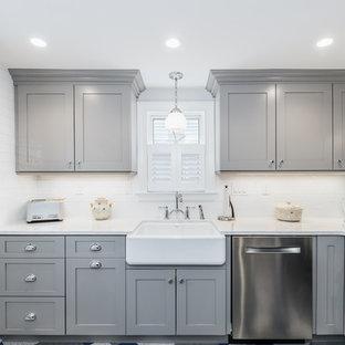 ブリッジポートの小さいトランジショナルスタイルのおしゃれなキッチン (エプロンフロントシンク、フラットパネル扉のキャビネット、グレーのキャビネット、クオーツストーンカウンター、白いキッチンパネル、サブウェイタイルのキッチンパネル、シルバーの調理設備、クッションフロア、アイランドなし、マルチカラーの床) の写真