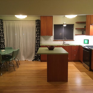 Design ideas for a mid-sized midcentury l-shaped eat-in kitchen in Richmond with a drop-in sink, flat-panel cabinets, medium wood cabinets, laminate benchtops, white splashback, ceramic splashback, stainless steel appliances, light hardwood floors, with island, brown floor and green benchtop.
