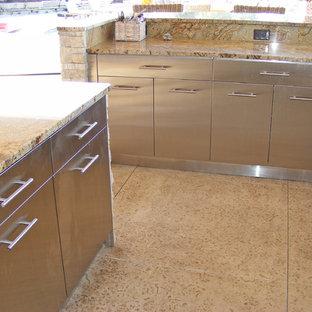 他の地域の中サイズのビーチスタイルのおしゃれなキッチン (シングルシンク、フラットパネル扉のキャビネット、ステンレスキャビネット、御影石カウンター、マルチカラーのキッチンパネル、石スラブのキッチンパネル、シルバーの調理設備の、コンクリートの床、ベージュの床、ベージュのキッチンカウンター) の写真