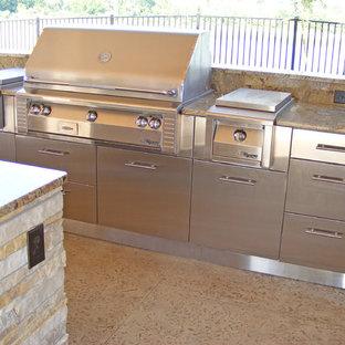 他の地域の中くらいのビーチスタイルのおしゃれなキッチン (シングルシンク、フラットパネル扉のキャビネット、ステンレスキャビネット、御影石カウンター、マルチカラーのキッチンパネル、石スラブのキッチンパネル、シルバーの調理設備、コンクリートの床、ベージュの床、ベージュのキッチンカウンター) の写真