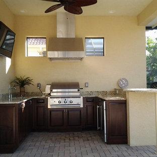 Bild på ett litet tropiskt u-kök, med en undermonterad diskho, luckor med upphöjd panel, skåp i mörkt trä, granitbänkskiva, beige stänkskydd, stänkskydd i sten, rostfria vitvaror, tegelgolv och en halv köksö