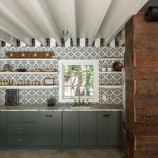 オースティンのインダストリアルスタイルのおしゃれなI型キッチン (アンダーカウンターシンク、フラットパネル扉のキャビネット、青いキャビネット、青いキッチンパネル、モザイクタイルのキッチンパネル、コンクリートの床、アイランドなし、グレーの床、ベージュのキッチンカウンター) の写真