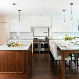 Inspiration for a large transitional u-shaped open plan kitchen in Toronto with an undermount sink, beaded inset cabinets, white cabinets, white splashback, stainless steel appliances, medium hardwood floors, multiple islands, quartzite benchtops, ceramic splashback and brown floor.