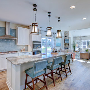Design ideas for a transitional l-shaped open plan kitchen in Baltimore with a farmhouse sink, louvered cabinets, white cabinets, blue splashback, subway tile splashback, stainless steel appliances, medium hardwood floors, with island, brown floor and grey benchtop.