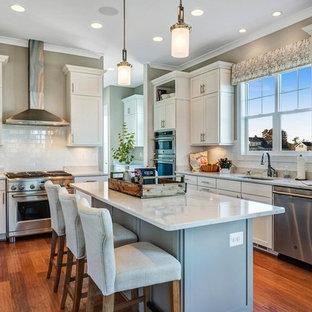 Idéer för ett klassiskt vit u-kök, med en undermonterad diskho, skåp i shakerstil, vita skåp, vitt stänkskydd, stänkskydd i tunnelbanekakel, rostfria vitvaror, mellanmörkt trägolv, en köksö och brunt golv