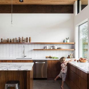 Retro Küche in L-Form mit flächenbündigen Schrankfronten, hellbraunen Holzschränken, Kücheninsel, Unterbauwaschbecken, Küchenrückwand in Weiß, Küchengeräten aus Edelstahl, Betonboden, grauem Boden und weißer Arbeitsplatte in Austin