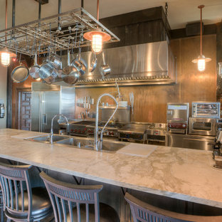 Industrial kitchen remodeling - Urban galley kitchen photo in Seattle with a triple-bowl sink, metallic backsplash and stainless steel appliances