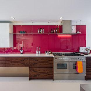 Exemple d'une très grande cuisine tendance en U avec un évier encastré, un placard à porte plane, un plan de travail en surface solide, une crédence rose, une crédence en feuille de verre, un électroménager en acier inoxydable et un îlot central.