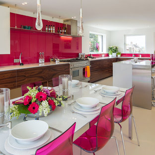 This is an example of an expansive modern u-shaped kitchen in London with an undermount sink, flat-panel cabinets, solid surface benchtops, pink splashback, glass sheet splashback, stainless steel appliances and with island.