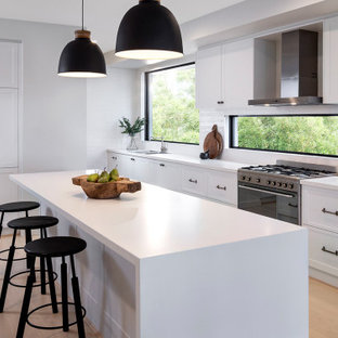 Photo of a large contemporary l-shaped kitchen in Other with a double-bowl sink, recessed-panel cabinets, white cabinets, mirror splashback, panelled appliances, with island, black floor and white benchtop.