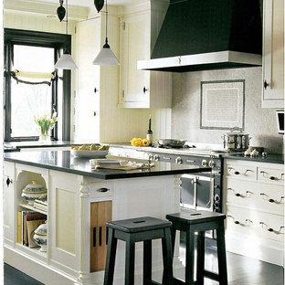 Idee per una cucina design con paraspruzzi con piastrelle a mosaico, ante gialle, ante con riquadro incassato e elettrodomestici neri