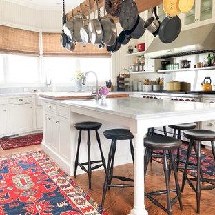 Idée de décoration pour une cuisine bohème avec un évier de ferme, un placard à porte shaker, des portes de placard blanches, un électroménager en acier inoxydable, un sol en bois brun, un îlot central, un sol marron et un plan de travail gris.