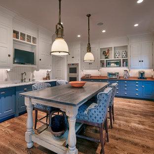 Geschlossene, Große Klassische Küche in U-Form mit Unterbauwaschbecken, profilierten Schrankfronten, blauen Schränken, Marmor-Arbeitsplatte, Küchenrückwand in Weiß, Elektrogeräten mit Frontblende, braunem Holzboden, Kücheninsel, Rückwand aus Holz, braunem Boden und weißer Arbeitsplatte in Philadelphia