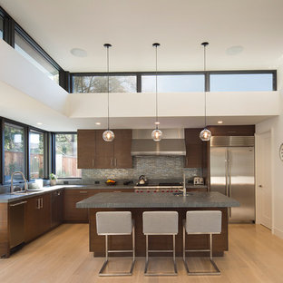 Design ideas for a large contemporary l-shaped enclosed kitchen in San Francisco with a submerged sink, flat-panel cabinets, dark wood cabinets, grey splashback, metal splashback, stainless steel appliances, an island, soapstone worktops, light hardwood flooring and grey worktops.