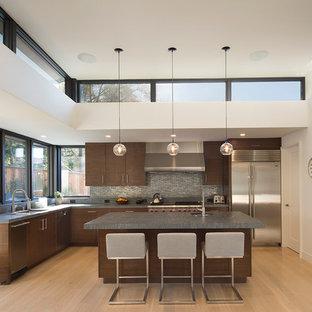 Große, Geschlossene Moderne Küche in L-Form mit Unterbauwaschbecken, flächenbündigen Schrankfronten, dunklen Holzschränken, Küchenrückwand in Grau, Rückwand aus Metallfliesen, Küchengeräten aus Edelstahl, Kücheninsel, Speckstein-Arbeitsplatte, hellem Holzboden und grauer Arbeitsplatte in San Francisco