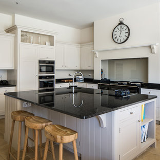 Photo of a large traditional l-shaped kitchen/diner in Other with recessed-panel cabinets, white cabinets, granite worktops, glass sheet splashback, black appliances, an island, beige floors, black worktops, a submerged sink and beige splashback.