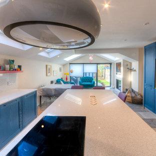 Diseño de cocina comedor en L, moderna, grande, con fregadero bajoencimera, armarios estilo shaker, puertas de armario azules, encimera de acrílico, salpicadero beige, salpicadero de azulejos de piedra, electrodomésticos negros, suelo de terrazo, una isla, suelo beige y encimeras beige