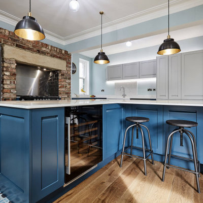 Inspiration for a large transitional l-shaped porcelain tile, blue floor and coffered ceiling eat-in kitchen remodel in Other with a farmhouse sink, shaker cabinets, blue cabinets, marble countertops, white backsplash, marble backsplash, stainless steel appliances, two islands and white countertops