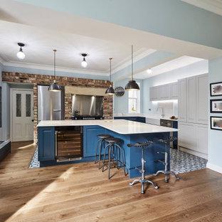 Bild på ett mellanstort vit vitt kök, med en rustik diskho, skåp i shakerstil, blå skåp, marmorbänkskiva, vitt stänkskydd, stänkskydd i marmor, rostfria vitvaror, klinkergolv i porslin, flera köksöar och blått golv