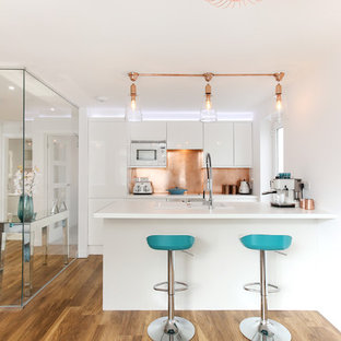 Design ideas for a contemporary kitchen in Other with a built-in sink, flat-panel cabinets, white cabinets, metallic splashback, white appliances, medium hardwood flooring, a breakfast bar and white worktops.