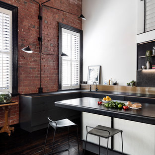 Photo of an industrial l-shaped kitchen in Melbourne with an undermount sink, flat-panel cabinets, black cabinets, black splashback, mosaic tile splashback, dark hardwood floors, with island, brown floor and black benchtop.