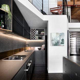 Inspiration for an industrial galley kitchen in Melbourne with an undermount sink, flat-panel cabinets, black cabinets, grey splashback, mosaic tile splashback, dark hardwood floors, with island, brown floor and brown benchtop.