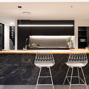 Inspiration for a contemporary galley kitchen in Brisbane with flat-panel cabinets, black cabinets, black splashback and with island.