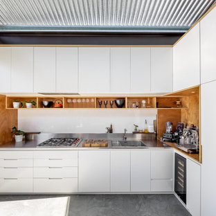 This is an example of a contemporary l-shaped kitchen in Sydney with an integrated sink, flat-panel cabinets, white cabinets, stainless steel benchtops, no island, grey floor and grey benchtop.