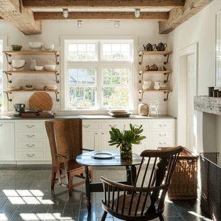 Idées déco pour une cuisine américaine linéaire campagne avec un placard à porte shaker, des portes de placard blanches, une crédence blanche, une crédence en carrelage métro, un sol en carreaux de ciment, un sol gris et un plan de travail gris.