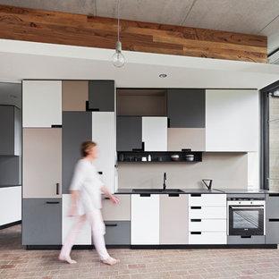 Aménagement d'une cuisine américaine parallèle contemporaine avec un évier encastré, un plan de travail en stratifié, un sol en brique, un placard à porte plane, des portes de placard grises, une crédence beige et aucun îlot.