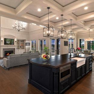 Offene Klassische Küche mit Landhausspüle, profilierten Schrankfronten, blauen Schränken, schwarzen Elektrogeräten, braunem Holzboden, Kücheninsel, braunem Boden und brauner Arbeitsplatte in Jacksonville