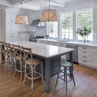 Mittelgroße Klassische Küche in L-Form mit Unterbauwaschbecken, Schrankfronten im Shaker-Stil, weißen Schränken, Küchenrückwand in Weiß, Küchengeräten aus Edelstahl, braunem Holzboden, braunem Boden, Marmor-Arbeitsplatte, Rückwand aus Keramikfliesen und Kücheninsel in Atlanta