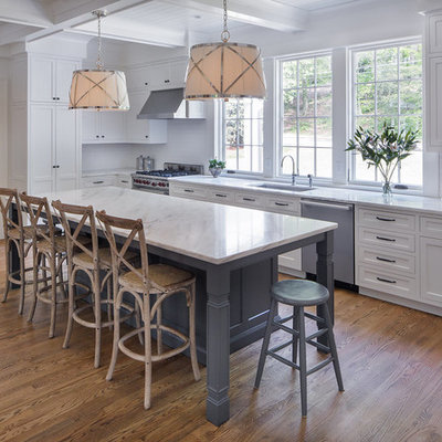 Inspiration for a mid-sized transitional l-shaped medium tone wood floor and brown floor kitchen remodel in Atlanta with an undermount sink, shaker cabinets, white cabinets, white backsplash, stainless steel appliances, marble countertops, ceramic backsplash and an island