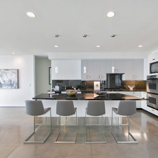 Contemporary kitchen ideas - Kitchen - contemporary l-shaped concrete floor and gray floor kitchen idea in Orange County with an undermount sink, flat-panel cabinets, gray cabinets, black backsplash, glass sheet backsplash, stainless steel appliances and an island