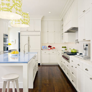 Contemporary kitchen designs - Inspiration for a contemporary l-shaped kitchen remodel in San Francisco with a farmhouse sink, recessed-panel cabinets, white cabinets, white backsplash, subway tile backsplash, paneled appliances and blue countertops