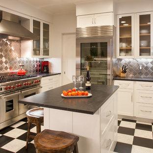 サンフランシスコのコンテンポラリースタイルのおしゃれなコの字型キッチン (ソープストーンカウンター、シルバーの調理設備、メタリックのキッチンパネル、メタルタイルのキッチンパネル、ガラス扉のキャビネット、白いキャビネット、マルチカラーの床) の写真