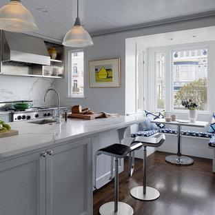 На фото: большая, серо-белая параллельная кухня в стиле неоклассика (современная классика) с обеденным столом, белым фартуком, двойной раковиной, фасадами в стиле шейкер, белыми фасадами, мраморной столешницей, техникой из нержавеющей стали, темным паркетным полом, островом и фартуком из мрамора с