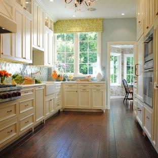 Esempio di una cucina parallela chic chiusa con ante con bugna sagomata, parquet scuro, nessuna isola, lavello stile country, top in marmo, paraspruzzi con piastrelle in ceramica, elettrodomestici da incasso e ante gialle