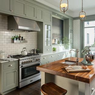 Foto på ett vintage kök, med en undermonterad diskho, skåp i shakerstil, gröna skåp, träbänkskiva, vitt stänkskydd, stänkskydd i tunnelbanekakel, rostfria vitvaror, mörkt trägolv och en köksö