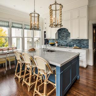 Idée de décoration pour une cuisine américaine victorienne avec un évier encastré, un placard avec porte à panneau encastré, des portes de placard blanches, une crédence bleue, une crédence en mosaïque, un sol en bois foncé, un îlot central, un sol marron et un plan de travail blanc.
