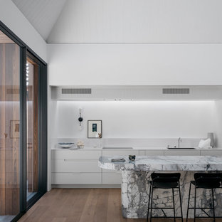 This is an example of a large contemporary single-wall eat-in kitchen in Sydney with an undermount sink, flat-panel cabinets, white cabinets, granite benchtops, white splashback, white appliances, light hardwood floors, with island, brown floor and white benchtop.