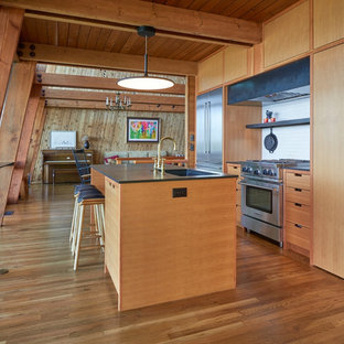 Midcentury modern kitchen designs - Example of a midcentury modern galley medium tone wood floor and brown floor kitchen design in Seattle with an undermount sink, flat-panel cabinets, medium tone wood cabinets, white backsplash, stainless steel appliances, an island and black countertops