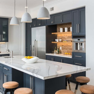 Transitional kitchen designs - Example of a transitional gray floor kitchen design in Los Angeles with an undermount sink, shaker cabinets, black cabinets, an island, white countertops and brown backsplash