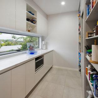 サンシャインコーストの中くらいのモダンスタイルのおしゃれなキッチン (白いキャビネット、クオーツストーンカウンター、シルバーの調理設備、セラミックタイルの床、ベージュの床、オープンシェルフ、ガラスまたは窓のキッチンパネル、アイランドなし) の写真