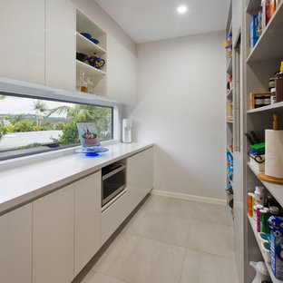 Mid-sized modern open concept kitchen appliance - Open concept kitchen - mid-sized modern galley ceramic floor and beige floor open concept kitchen idea in Sunshine Coast with white cabinets, quartz countertops, stainless steel appliances, open cabinets, window backsplash and no island