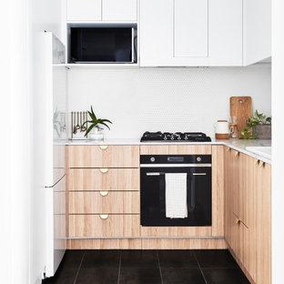 Inspiration för avskilda, små moderna vitt u-kök, med en nedsänkt diskho, skåp i ljust trä, vitt stänkskydd, stänkskydd i mosaik, svarta vitvaror, cementgolv, grått golv och släta luckor