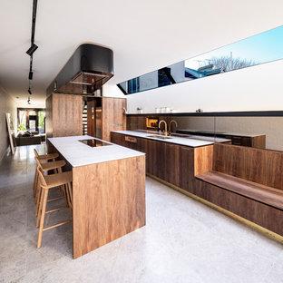 Immagine di una cucina parallela moderna con ante lisce, ante marroni, top in marmo, paraspruzzi a effetto metallico, paraspruzzi a specchio, isola, top bianco, lavello a doppia vasca e elettrodomestici da incasso